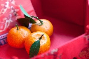Mini mandarin oranges in a red chinese box with new  year money packet