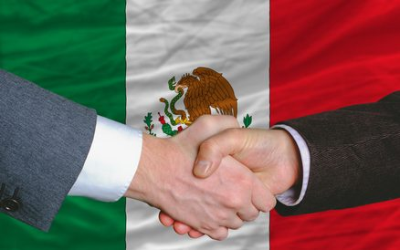 businessmen handshake after good deal in front of mexico flag