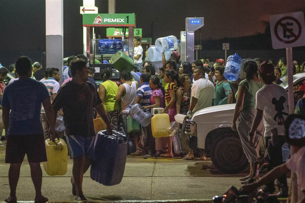 Residents steal gasoline and diesel from a gas station following protests against an increase in fuel prices in Allende, southern Veracuz State, Mexico, late on Jan. 3. Photo Source: Erick Herrera / AP